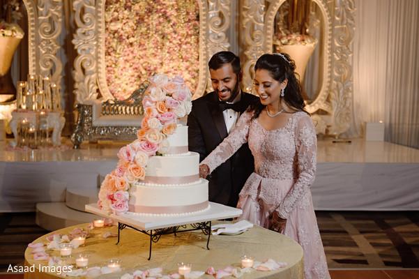 Indian wedding reception cutting the cake scene.