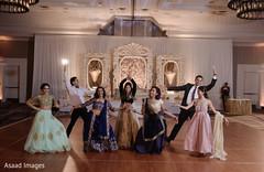 Gleeful indian wedding reception dance performance.