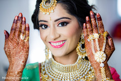 Indian bride showing her jewelry and mehndi