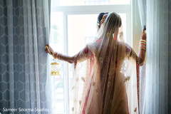 Indian bride looking through the window