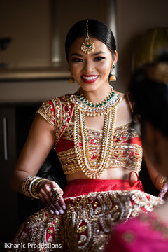 Joyful Indian bride with her open shirt lehenga.