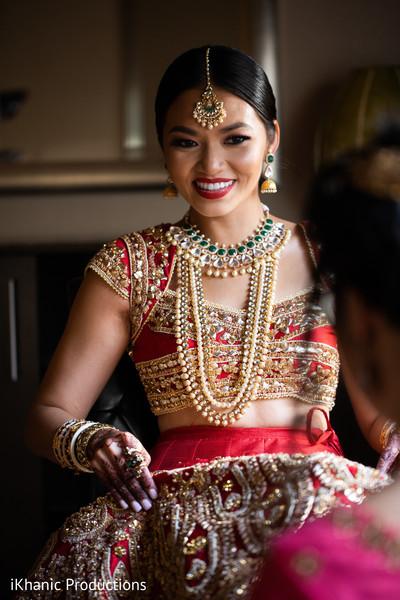 Joyful Indian bride with her open shirt lehenga.