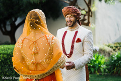 Sweet  Indian bride's and groom's first look scene.