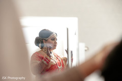Indian bride getting help to get ready for ceremony.