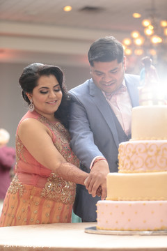 Indian lovebirds cutting cake moment.