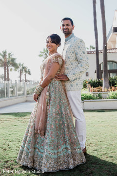 Indian couple taking pictures outside