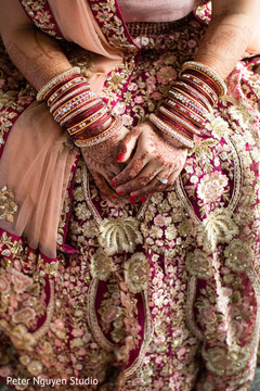 Indian bride showing her mehndi design and lengha
