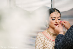 Beautiful Maharani being assisted with the bridal jewelry