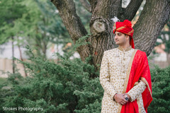Indian groom posing outside by the trees