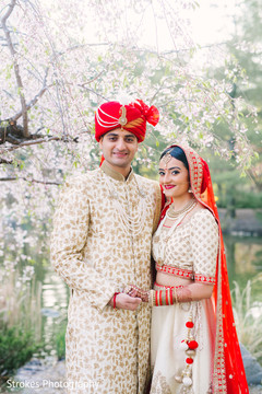Indian bride holding hands with Raja outdoors