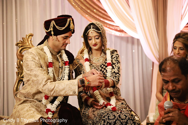 Indian groom putting bracelet to bride capture.
