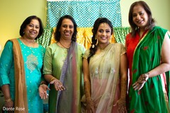 Indian wedding guests with bride showing their mehndi art.