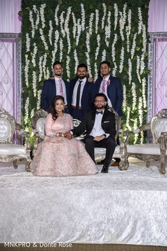Indian bride and groom posing with groomsmen.