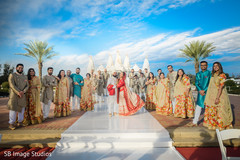 Indian couple taking pictures with bridesmaids and groomsmen