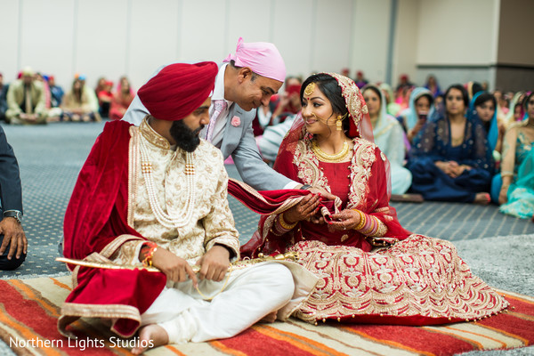 Lovely Indian bride garbing groom's ghoonghat.