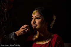 Indian bride getting her ceremony makeup done.