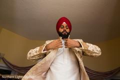 Indian groom putting his sherwani on.