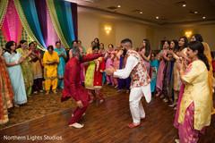Indian groom dancing at sangeet capture.