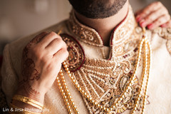 Indian groom being assisted with the accessories