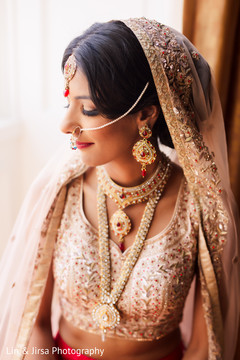 Indian bride posing with her jewelry prior to the ceremony