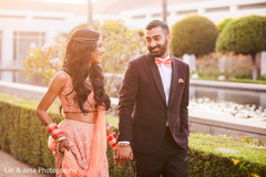 Indian bride and groom holding hands outdoors