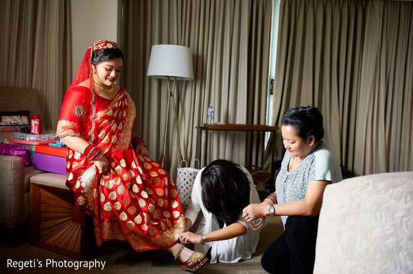 Maharani being assisted with her shoes prior to the ceremony