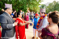 Indian groom arriving and being greeted by maharani's family