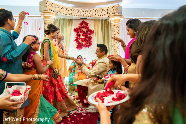 Indian groom putting ring to bride.