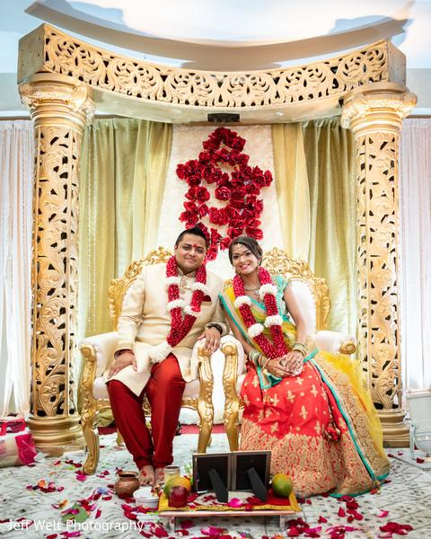 Enchanting indian couple posing at their wedding ceremony mandap.