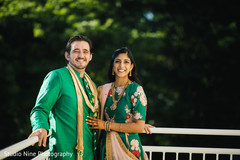 Gorgeous Indian bride and groom posing outdoors of the sangeet .