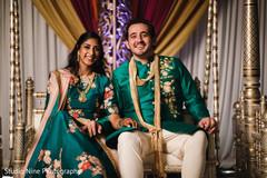 Joyful Indian couple in their sangeet swing seat.