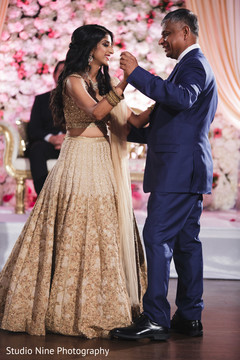 Cute Indian bride dancing with her father.