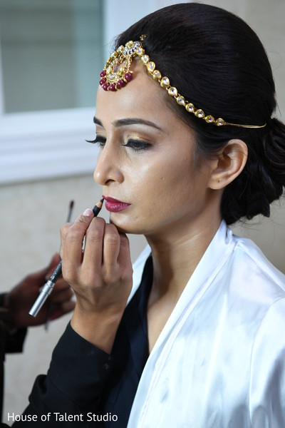 Indian bride getting her lips colored capture.