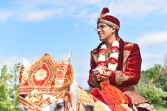 Charming groom riding on his white baraat horse.