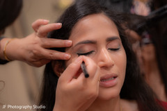 Indian bride getting her eyes makeup done.