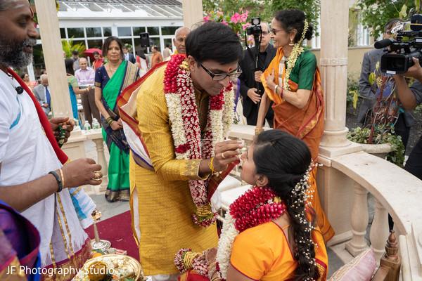 Indian groom applies sindoor in the bride's forehead.
