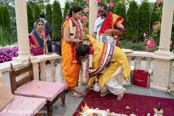 Indian bride being put a ring on to her toe.