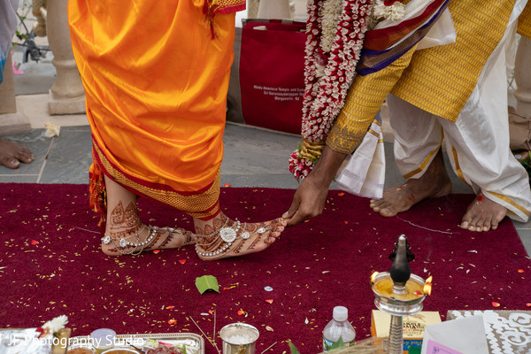 Indian groom holding Indian bride's toe.