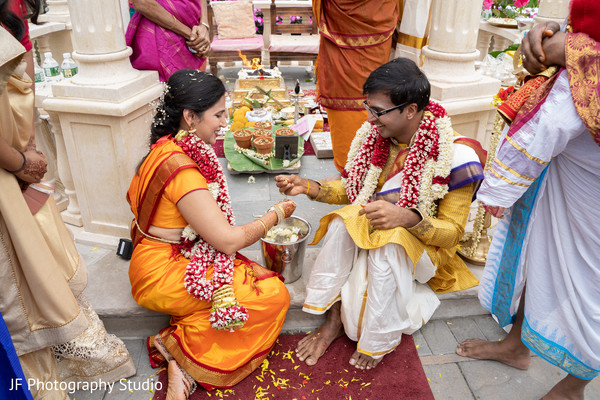 Indian bride and groom getting items from water ritual.