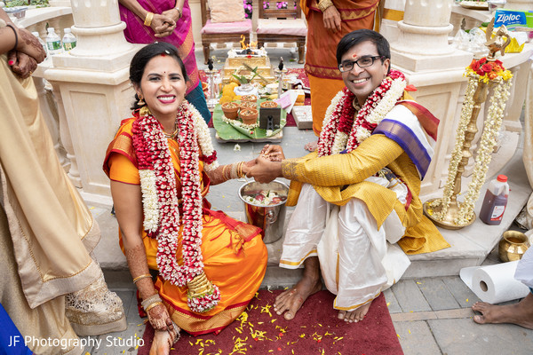 Indian bride and groom putting rings on.