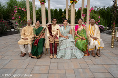 Adorable Indian bride and groom posing with family.