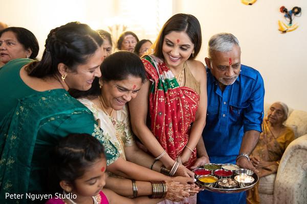 Indian bride holding pre-wedding Haldi ritual items.