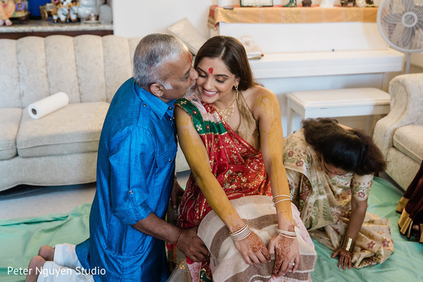 Indian bride being kiss by her father at the Haldi party.