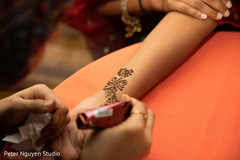 Indian bride getting her mehndi art done.
