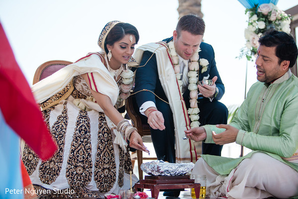 Indian bride and groom making offerings to sacred fire.