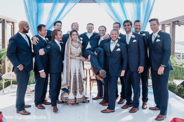 Indian bride and groom posing with groomsmen.