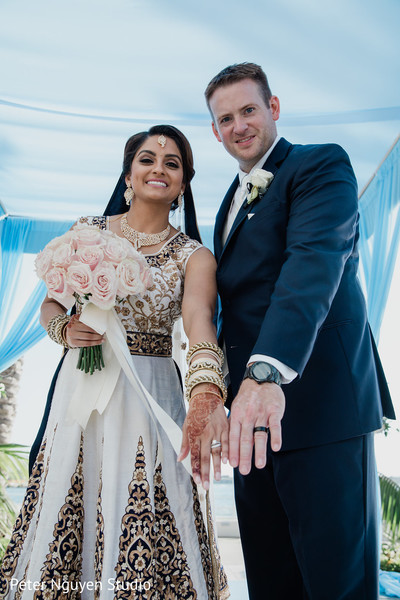 Indian bride and groom showing their wedding rings.