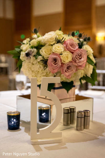 Graceful floral centerpiece and table number.