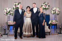 Adorable Indian bride and groom posing with family members.