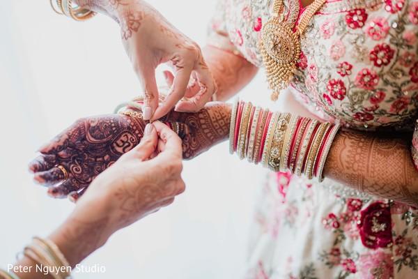 Indian bride putting her Hath Panja bracelet.